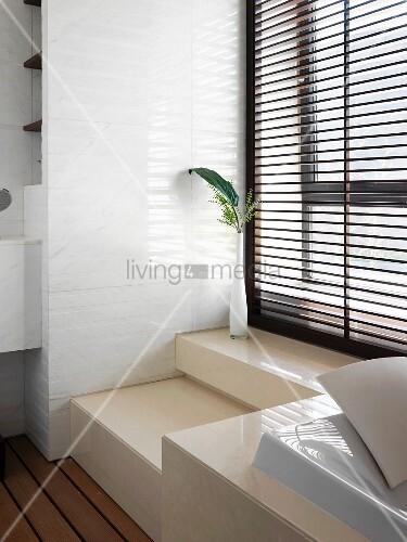 im podest eingebaute badewanne vor fenster mit geschlossener jalousie im minimalistischen bad. Black Bedroom Furniture Sets. Home Design Ideas