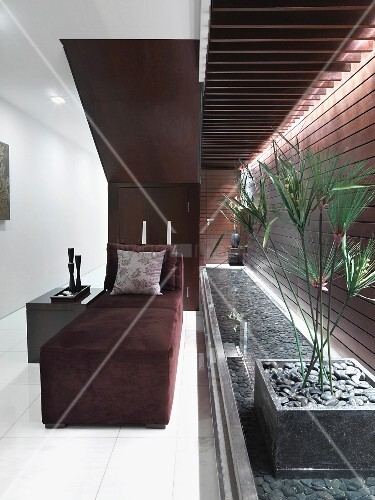 Modern velvet lounge chair near indoor water feature