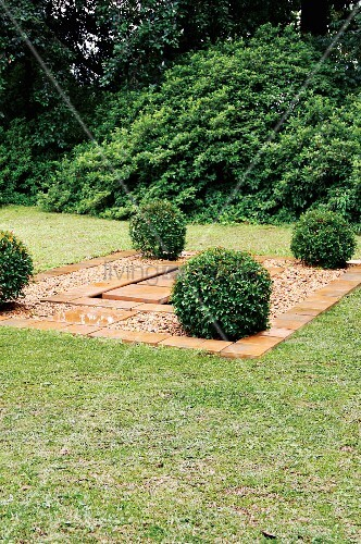 Geometric water feature created from stone flags and gravel bordered by box bushes