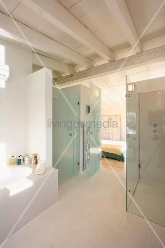 Modernes Bad mit Holzbalkendecke über verglastem Duschbereich und ...