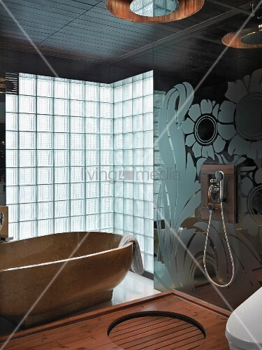 Hand-held shower head on a floral-patterned glass wall and a shower head above a wooden shower area with a stone bathtub in front of glass brick wall in the background