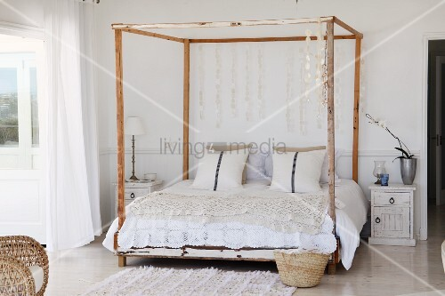 Romantic crocheted throw and capiz shell discs hanging from frame of four-poster, vintage bed