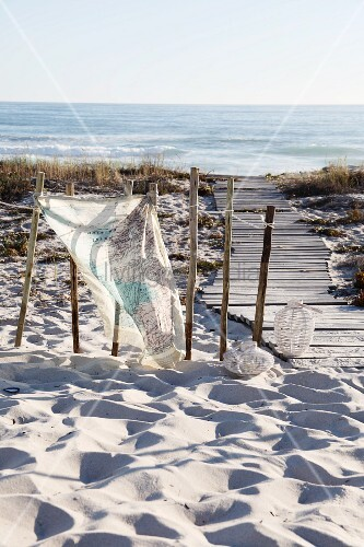 Cloth printed with map motif tied to old wooden post next to wooden walkway leading through sand dunes to sea