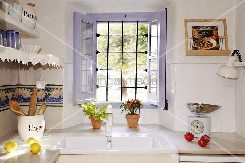 mediterrane k che mit wei em sp lbecken und mit spitzen verziertem wandboard ge ffnetes fenster. Black Bedroom Furniture Sets. Home Design Ideas