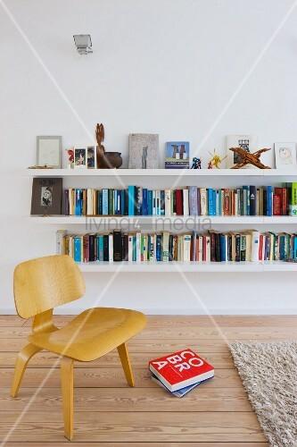 Niedriger Bauhaus Stuhl aus Holz vor weissen Regalböden an Wand mit Büchern