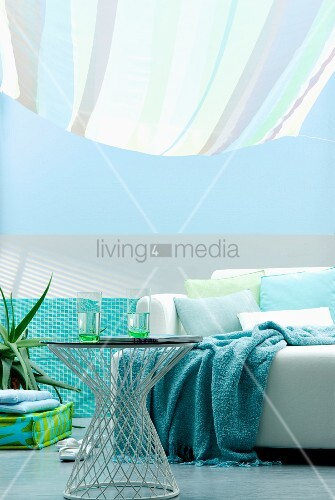 Living area in shades of aqua with sofa and side table below striped awning