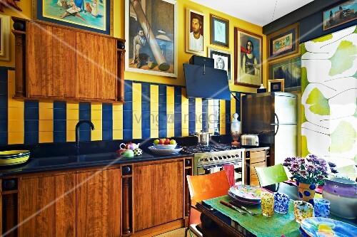 Moderne Holzküche Mit Großer Bildersammlung An Den Wänden; Im Vordergrund  Ein Gedeckter Tisch Mit Farbenfrohem Keramikgeschirr