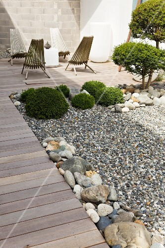 Garden Chairs On A Landscaped Terrace With Boxwood Topiaries In A