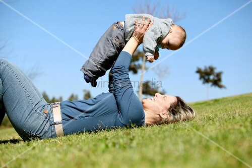A woman lying in a field playing with a baby