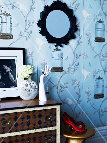 Hand ornament as jewellery stand on vintage chest of drawers against romantic wallpaper with birdcage motif
