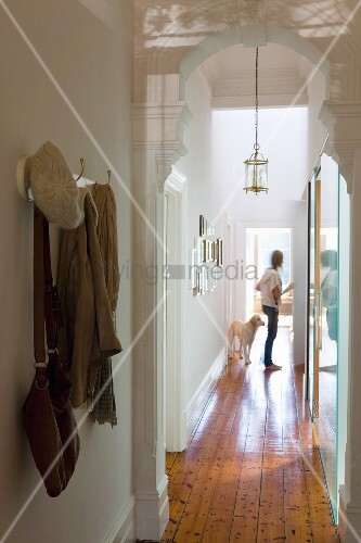 View through white, carved wooden archway of woman and dog in narrow hallway of renovated period building