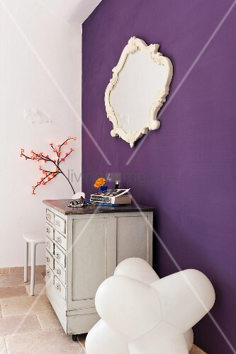 White commode, framed mirror and designer chair by a violet wall