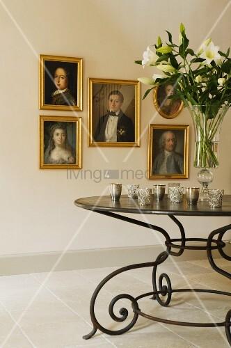 historische lportraits mit goldrahmen an weisser wand im vordergrund ein schmiedeeiserner. Black Bedroom Furniture Sets. Home Design Ideas