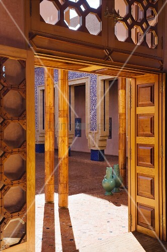 Octagonal window panes above wooden doors leading out to courtyard