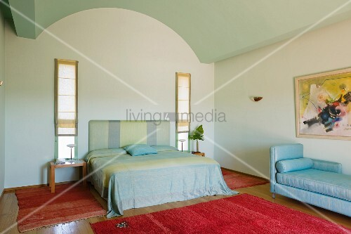 Simple bedroom with red handmade rugs and pale fabrics on the bed and daybed