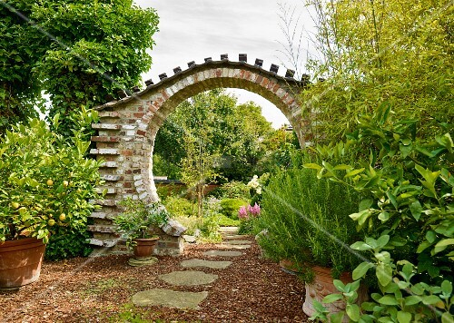 Oriental-style circular archway in summery ornamental garden with meditative atmosphere and path of rough stone slabs