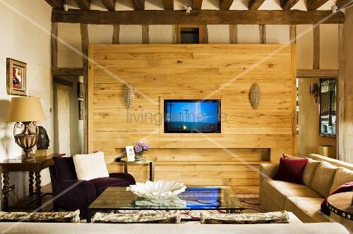 Schlichtes Sofa und Sessel am Couchtisch mit Glasplatte vor Holz ...
