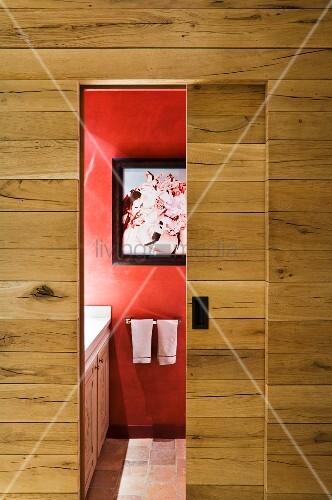 schlichte holzwand mit offener schiebet r und blick auf rote wand mit bild im bad bild kaufen. Black Bedroom Furniture Sets. Home Design Ideas