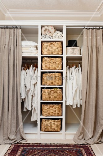 White shirts and linens hanging on rails in open storage with curtains. Wicker baskets form drawers on open shelving