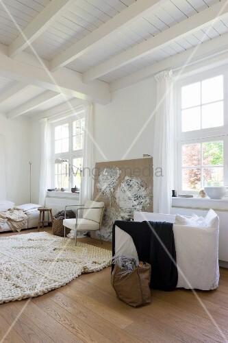 Tasche auf Boden neben weissem Polstersessel in schlichtem Wohnzimmer mit weisser Holzdecke ...