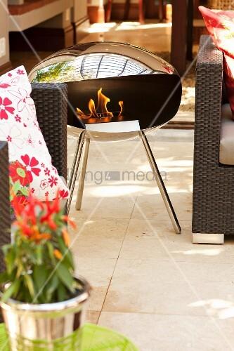 Tragbare Feuerstelle aus Edelstahl auf Veranda zwischen ...
