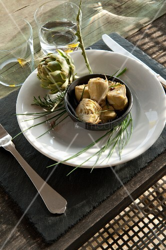 An artichoke as a starter on a table laid Mediterranean-style