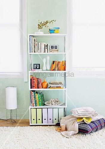 Bücher und Stehordner in modernem Regal vor pastellblauer Wand und Kissenstapel auf Flokatiteppich