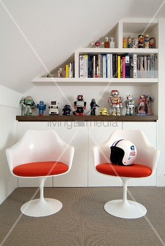 White plastic shell chairs with red cushions in front of sideboard and shelving on wall of attic room