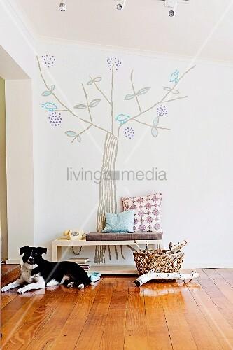 Fröhlicher Baum als Wanddekoration; davor eine kleine Sitzbank mit Sitzpolster und Kissen