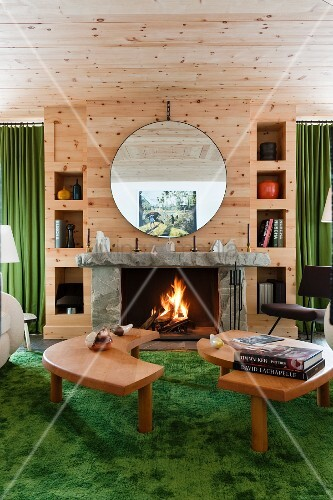 Two-part coffee table on green rug in front of open fire below circular mirror on wooden wall
