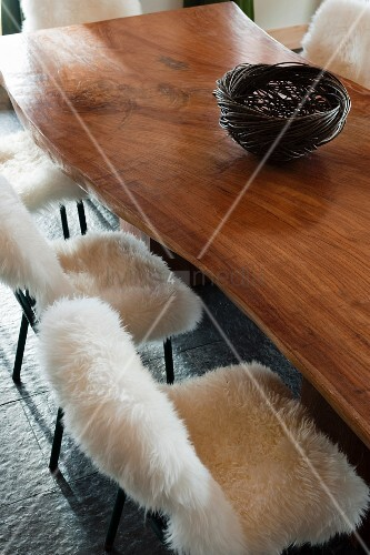 Wicker basket on polished table top and metal chairs with fluffy lambskin covers