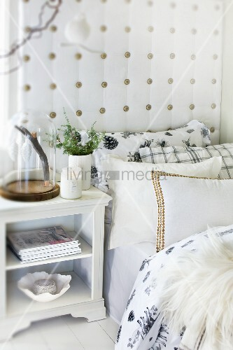 Many scatter cushions on bed with upholstered headboard and bedside cabinet in Scandinavian country-house style