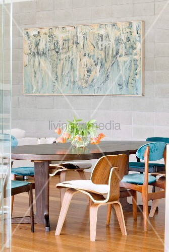 Bauhaus wooden chairs around dining table and modern artwork on pale grey stone wall