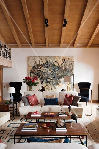 60s-style coffee tables and various scatter cushions on sofa in living room with wood-beamed ceiling