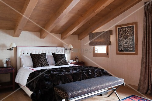 Upholstered bench at foot of double bed in attic room with wood-beamed ceiling
