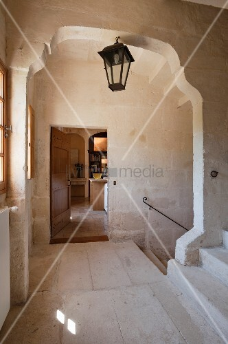 Staircase landing with walls and floor of pale stone; dark, lantern-style lamp in middle