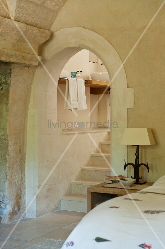 View from a rustic bedroom of an archway and stone stairway to the en suite bathroom