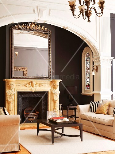 Mirror on ornately carved mantelpiece behind classic lounge area with two sofas