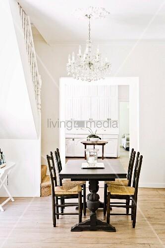 dunkler esstisch mit st hlen in hellem raum mit kronleuchter und durchgang zur wei en k che. Black Bedroom Furniture Sets. Home Design Ideas