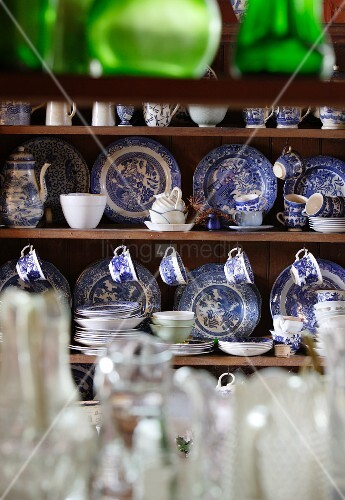 Classic blue and white china dinner service in open-fronted dresser
