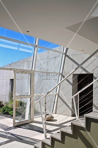 Staircase in contemporary building with glass wall and view into courtyard