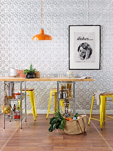 Kitchen table with wooden top and storage below on metal shelving; metal stools and industrial-style, retro pendant lamp in front of embossed metal wall panels
