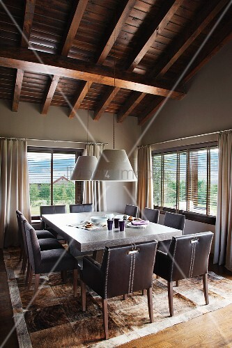Spacious dining area with patchwork, animal skin rug and comfy, upholstered chairs under a dark wood beam ceiling