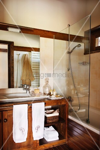 Bathroom with vanity, next to it a bathtub with a glass wall panel