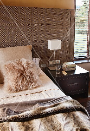 Bedroom in natural shades - fur cushion and cosy blanket on double bed with wide, upholstered headboard