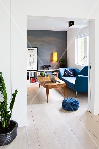 View of 50s-style wooden table in front of blue, curved sofa through wide open doorway
