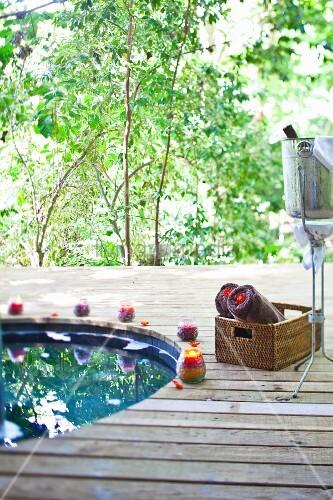 Holzterrasse mit rundem Bassin, Korb mit Handtuchrollen und Sektkühler auf Metallständer vor grünen Bäumen