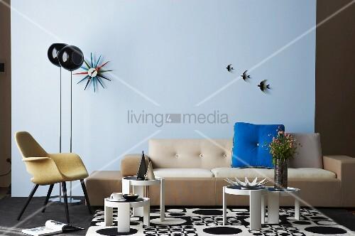 Sofa, Retrosessel und kleine, runde Stapeltische auf gemustertem Schwarzweiss Teppich, ergänzt mit 60er Jahre Accessoires