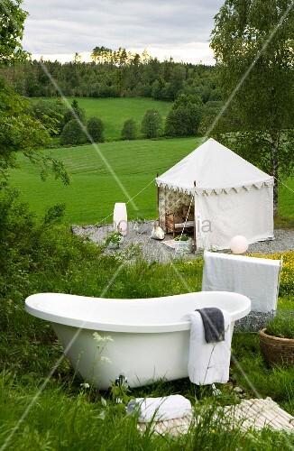 Vintage Badewanne auf einem Berghang und Blick auf zeltartigen Pavillon auf der grünen Wiese