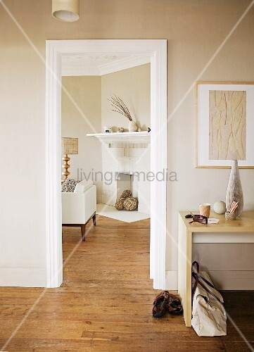 Moderner Schreibtisch Im Vorraum Neben Offener Tür Mit Blick Auf  Durchgehenden Dielenboden Und Offenen Kamin Im Beigehaltenen Wohnzimmer